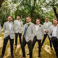Groom and groomsmen all pose for a photo dressed in pinstirpe blazers, trees stand behind them