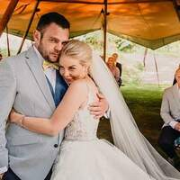 A bride & groom hug and celebrate their union underneath a Tipi ceremony