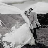 A bride & groom kiss, her veil blows with the wind as they stand in a field on the Finnebrogue Woods Estate