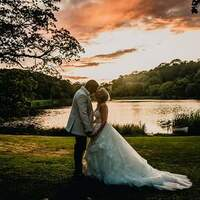 A bride & groom spose together in front of Finnebrogue Lake at sunset
