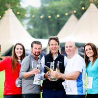 Runners and owner of Finnebrogue Woods celebrate with a drink in front of the tipi venue