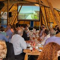 Down Rural corporate guests sit and watch a video inside the tipi venue at Finnebrogue Woods