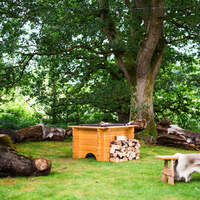 A bamsemax open firepit sits with logs are piled up beside it, large logs and benches for sitting are around it for guests