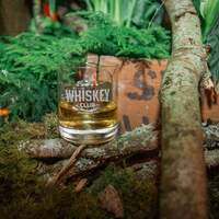 A glass full of whiskey sits among moss and wood at the Whiskey in the Woods corporate promotional event