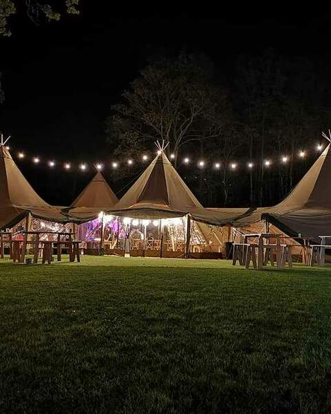The four giant hat tipis are lit up with festoon lighting strung from the tops of the tipis, picnic benches sit in front