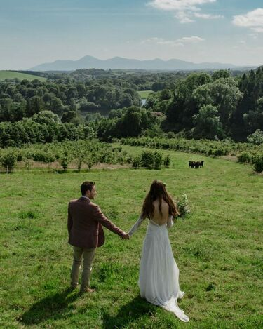 A bride & groom hold hands at the top of a hill overlooking the beautiful Northern Irish countryside
