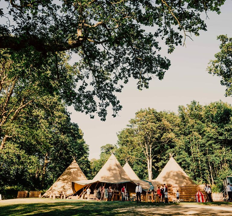 Wedding guests celebrate on a beautiful summers day in our four tipi wedding venue amongst the trees at Finnebrogue Woods