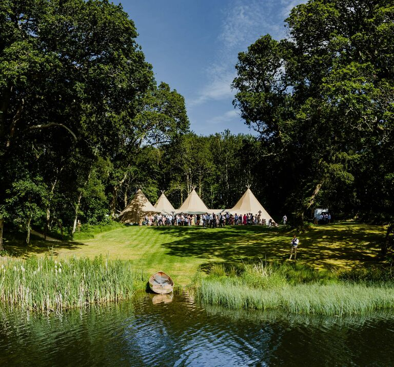 Four tipis sit amongst ancient wood land with a magical lake in the forefront, wedding guests are standing outside celebrating