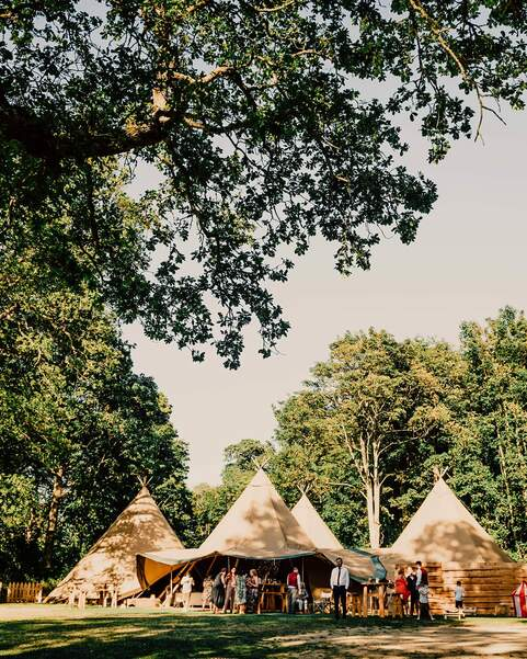 Four tipis sit amongst ancient woodland with a magical lake in the forefront, wedding guests are standing outside celebrating
