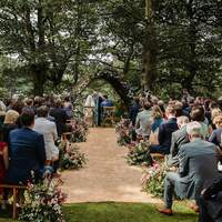 A ceremony takes place at Finnebrogue Woods, the aisle and wicker arch are decorated with colourful wild flowers