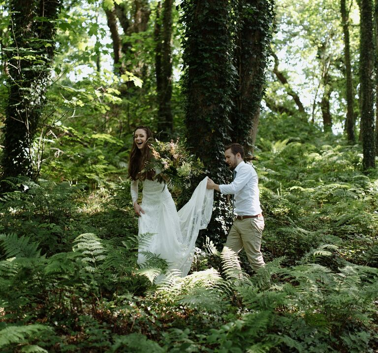 A bride and groom walk among lush green ancient woodland of Finnebrogue Woods, the groom holds the brides train up