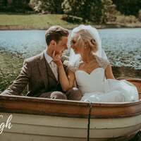 Newly married couple smile & gaze at eachother while sitting in a rowing boat on Finnebrogue Lake