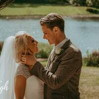 Wedding couple pose underneath a wicker arch at Finnebrogue Woods