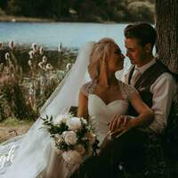Bride & groom sit together against a tree overlooking a glistening lake