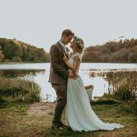 Bride & groom stand and pose for a photograph in front of finnebrogue Woods lake