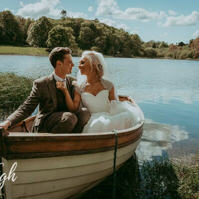 Newly married couple gaze at eachother while sitting in a rowing boat on Finnebrogue Lake
