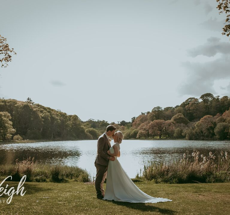 Bride & groom kiss in front of Finnebrogue Woods Lake during the autumn