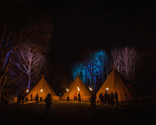 Three Tipis and the trees behind them are lit up with uplighters, corporate guests are silhouetted by fire torches