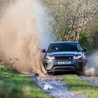 A black Range Rover drives along a trail at Finnebrogue Woods, puddles splash on either side of it