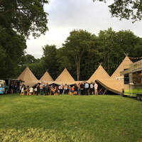 Wedding guests celebrate in front of the open sided Tipi wedding venue, two food trucks stand either side