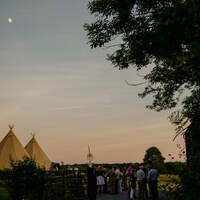 Three tipis stand in the distance with guests and trees in the foreground during sunset