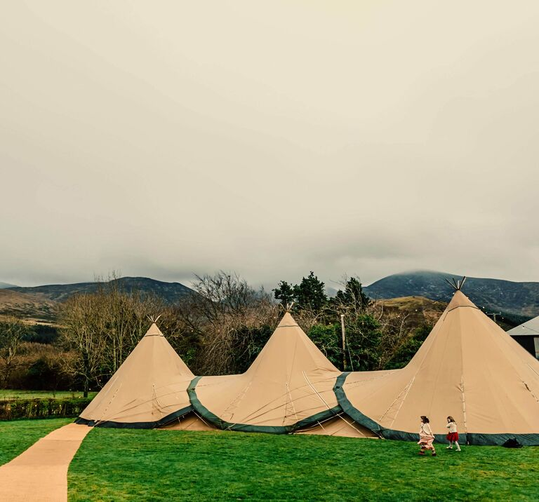 Three tipis stand in a field with the Mourne Mountains behind them, they create a charming outdoor structure perfect for a wedding