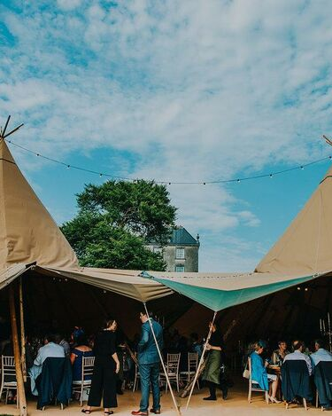 Open sided entrance to a tipi wedding reception, inside is crowded with guests sitting at tables